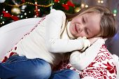 Little girl sleeping on Christmas tree background