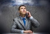 Young troubled wet businessman talking on phone