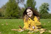Young beautiful girl lying on the grass in autumn park