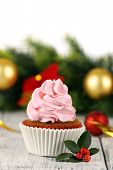 Cup-cake with Christmas decoration on wooden surface background