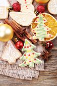 gingerbread cookies with Christmas decoration on burlap cloth and wooden table background