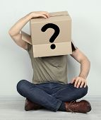 Man with cardboard box on his head sitting on floor near wall