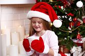 Little girl in Santa hat and mittens taking cup sitting near fir tree on fireplace with candles background