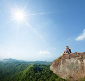 Young hiker sitting on top of the mountain at sunny day