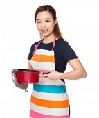 Asian Housewife holding saucepan with oven gloves