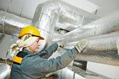 Thermal insulation. Female insulation worker isolating industrial pipe with glass wool and foil