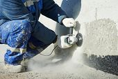 stock photo of construction machine  - Builder worker with grinder machine cutting finishing concrete wall at construction site - JPG