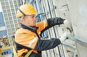 picture of thermal  - worker builder making construction for ventilation facade on a building with screwdriver drill - JPG