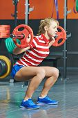 Young woman training exercises with weight bar in fitness club gym