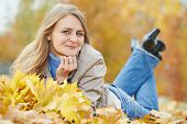 Smiling adult woman with autumn maple leaves wreath in park at fall outdoors