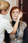 Makeup technique. Applying eye shadow on redheaded woman