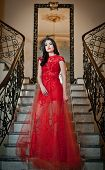 The beautiful girl in a long red dress posing in a vintage scene. Young beautiful woman