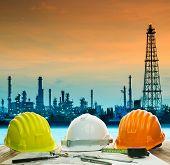 Safety Helmet On Engineer Working Table Against Beautiful Oil Refinery In Industry Estate