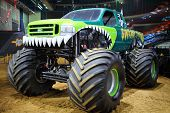 MOSCOW, RUSSIA - MAR 29, 2014: Green car with huge wheels, participant show Monster X Tour in Moscow