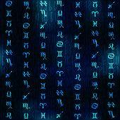Glow zodiac symbols on navy blue blur background.