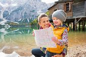 picture of south tyrol  - Portrait of happy mother and baby with map on lake braies in south tyrol italy - JPG