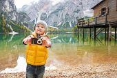 stock photo of south tyrol  - Happy child taking photo while on lake braies in south tyrol italy - JPG