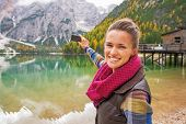 stock photo of south tyrol  - Happy young woman taking photo on lake braies in south tyrol italy - JPG