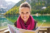 foto of south tyrol  - Portrait of happy young woman with map on lake braies in south tyrol italy - JPG