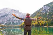 foto of south tyrol  - Young woman on lake braies in south tyrol italy rejoicing - JPG