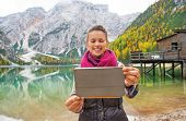 Happy Young Woman Taking Photo With Tablet Pc On Lake Braies In