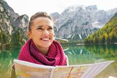 Portrait Of Happy Young Woman With Map On Lake Braies In South Tyrol, Italy