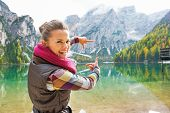 stock photo of south tyrol  - Portrait of happy young woman on lake braies in south tyrol italy framing with hands - JPG