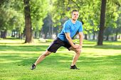 Full length portrait of a young smiling athlete exercising in a park