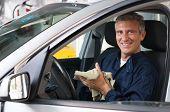 Portrait Of Mature Mechanic Sitting In Car At Workshop