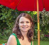 Attractive Woman Sits In Her Garden Under A Parasol