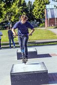 picture of scooter  - boy has fun riding his push scooter at the skatepark - JPG
