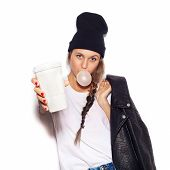 stock photo of swag  - swag girl in black beanie giving cup of coffee and inflating bubble of chewing gum - JPG