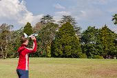 stock photo of glider  - Boy teenager throws his model glider aircraft into sky at home - JPG