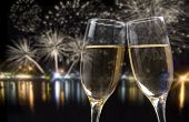 Glasses with champagne against fireworks and city lights