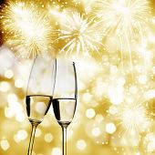 Toasting with two champagne glasses against fireworks and holiday lights