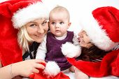 Smiling Infant Baby With Two Womans With Santa Hats