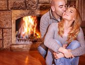 image of chalet  - Portrait of gentle couple sitting near fireplace and kissing on luxury ski resort - JPG