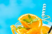 Fresh orange Mojito cocktail  with twist by the swimming pool