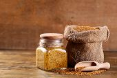 image of mustard seeds  - Mustard seeds in bag and Dijon mustard in glass jar on wooden background - JPG
