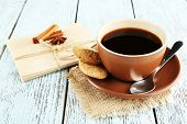 Cup of coffee with spoon and cookies on burlap cloth near envelopes on color wooden background
