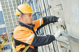 stock photo of labourer  - worker builder making construction for ventilation facade on a building with screwdriver drill - JPG