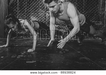 poster of Sportsmen. fit male trainer man and woman doing clapping push-ups explosive strength training concep
