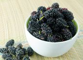picture of mulberry  - Fresh Fruits Sweet and Ripe Black Mulberries in A White Bowl on Brown Straw Mat - JPG