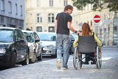 picture of rollator  - boy is walking next to a girl on a wheelchair - JPG