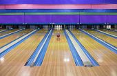 stock photo of bowling ball  - Generic Bowling Alley lanes with bowling ball going towards the pins - JPG
