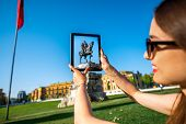 picture of albania  - Young woman tourist photographing with digital tablet Skanderbeg monument in Tirana - JPG