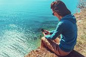 stock photo of compasses  - Young woman sitting on coast near the sea and searching direction with a compass - JPG