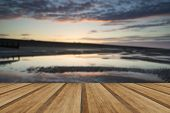 pic of tide  - Beautiful sunrise reflected in low tide water pools on beach landscape with wooden planks floor - JPG