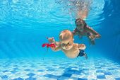picture of mother baby nature  - In the pool young mother teaches to swim 10 month old baby  - JPG