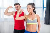foto of sportive  - Active athletic sportive woman girl and man showing their muscles biceps healthy lifestyle looking at camera.